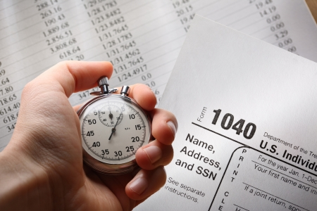 tax forms: Hand with stopwatch on tax form and budget