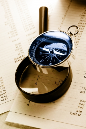 Operating budget, magnifying glass and black compass