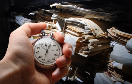 Hand with stopwatch, paper documents stacked in archive 스톡 콘텐츠