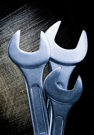 scratchy: Metallic wrenches on scratchy black background