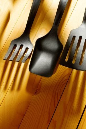 Kitchen utensil collection on wooden background photo