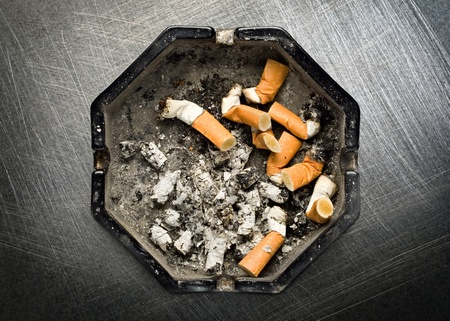 Ashtray on steel scratchy background photo