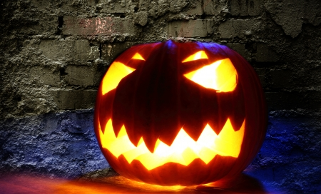 Angry halloween pumpkin on wall background photo