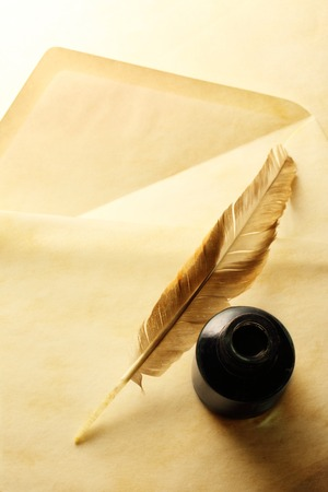 Blank envelope with inkwell and feather photo