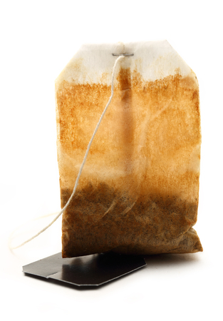 Used tea bag with label on white photo