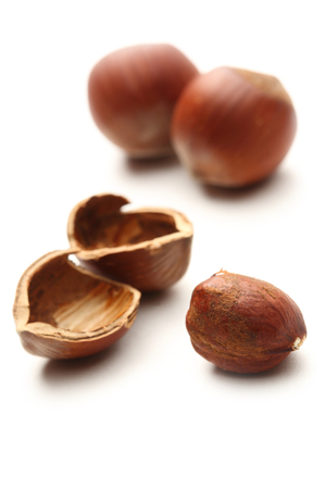 Whole and cracked hazelnuts on white photo