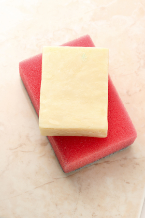 Bar of soap and sponge on tile photo