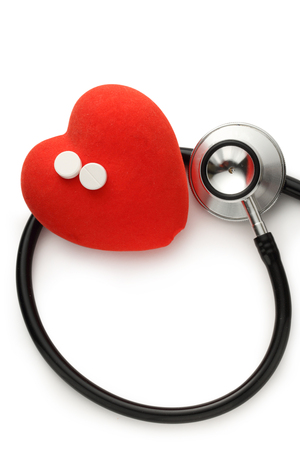 Red heart, stethoscope and pills on white background photo