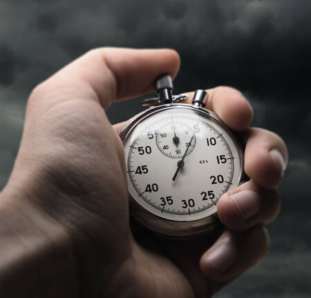 Hand holding stopwatch on stormy sky background photo