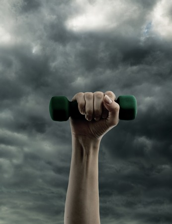 Dumbbell in hand on cloudy sky photo