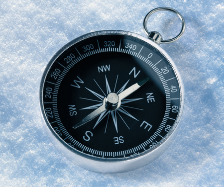 Black compass on snow background photo