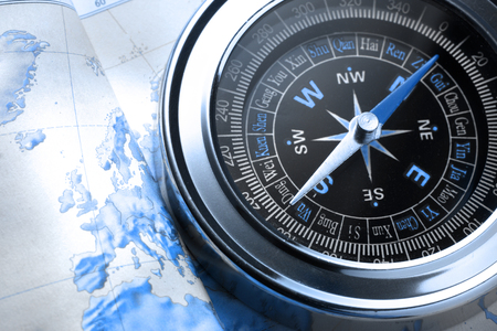 Compass on map background in blue toning photo