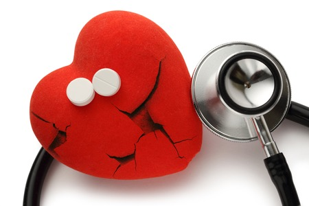 Red broken heart, stethoscope and pills on white photo