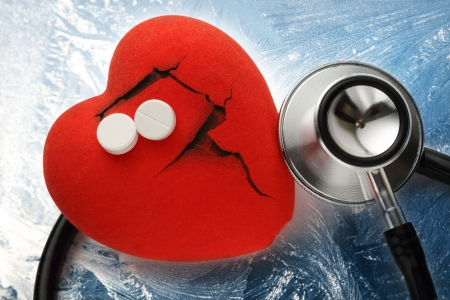 Red broken heart, stethoscope and pills on ice photo