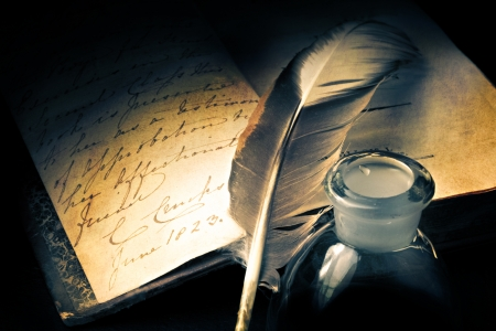 inkpot: Old book with feather and inkpot