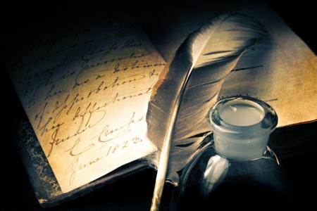 Oud boek met veer en inktpot