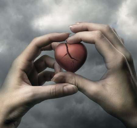 Broken red heart in hands on stormy sky photo