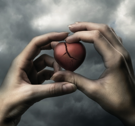 Broken red heart in hands on stormy sky Stock Photo