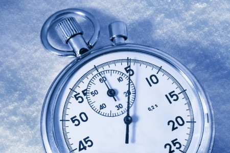 Stopwatch on snow in blue toning photo