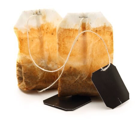 pack string: Used tea bags with label on white Stock Photo