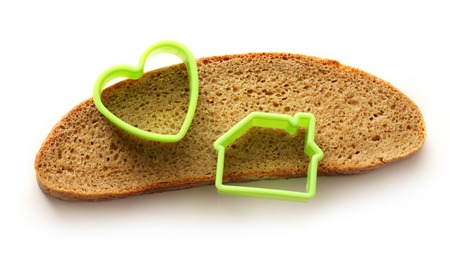 Slice of bread in house and heart form on white photo