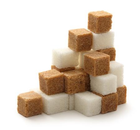 Cane and white sugar cubes Standard-Bild