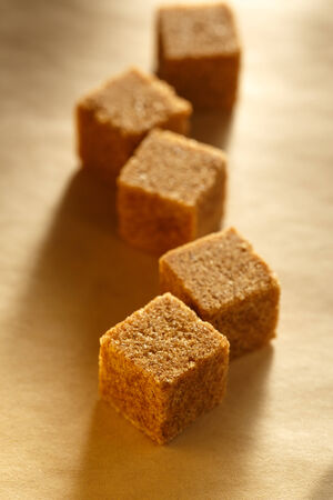 Cane sugar cubes on paper photo