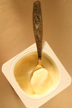 Yogurt pot with full spoon photo