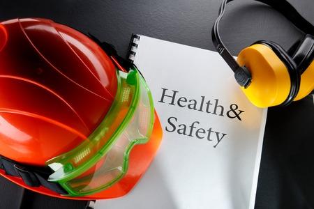 casco rojo: Gafas de seguridad, auriculares y casco rojo Foto de archivo