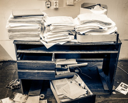 Messy workplace with stack of paper photo