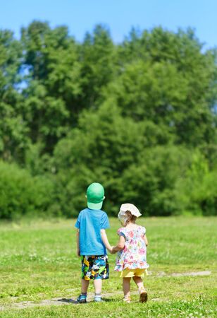 boy and girl holding hands: Little boy and girl walking in the park hand in hand Stock Photo