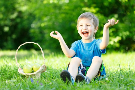Little boy sitting on the grass with basket of apples photo