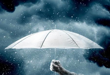 Umbrella in hand under raindrops of thunderstorm photo