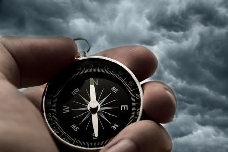 Hand holding black compass on thunder sky background photo