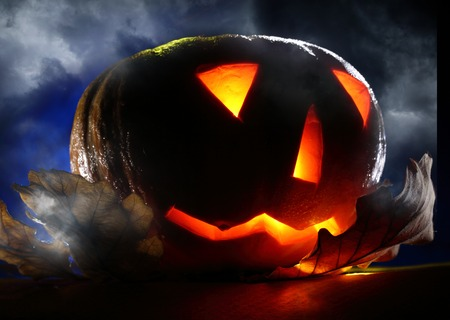 Halloween pumpkin on leaves at night photo