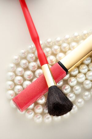 make over: Make up brush and lipstick over white pearl necklace Stock Photo
