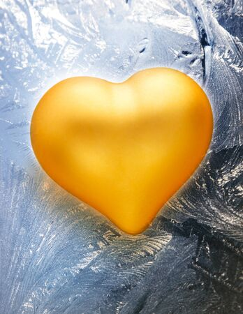frosted window: Golden toy heart on frosty window background