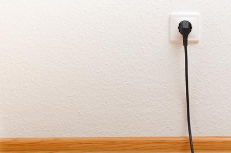 Single electric socket with plug on white wall Stockfoto