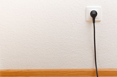 Single electric socket with plug on white wall Foto de archivo