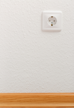 grounded plug: Single empty electric socket on white wall
