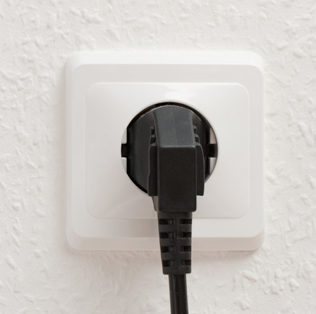 Single electric socket with plug on white wall photo