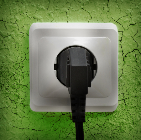 crannied: Wall plug socket on cracked colored wall background