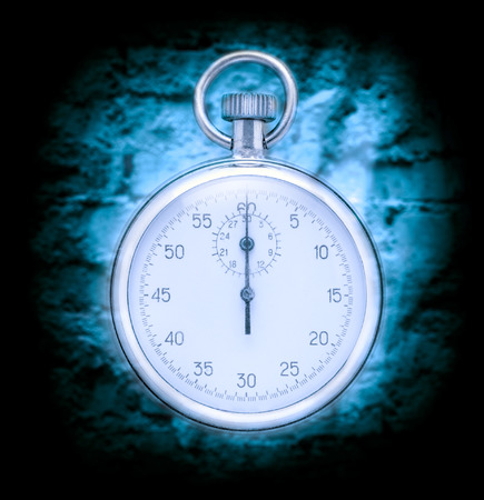 stop time: Stopwatch on cracked wall background in blue toning