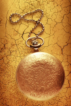 cracky: Golden pocket watch with chain on cracked background