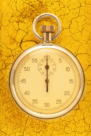 crannied: Stopwatch closeup on the cracked yellow background