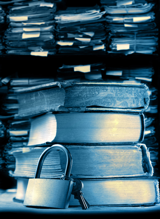 Pile of old books and keylock on archive folders background photo