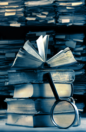 depository: Old books with magnifying glass in archive
