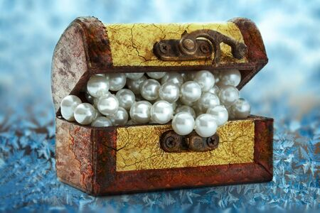 ice chest: Wooden chest with white pearl necklace on frozen window Stock Photo