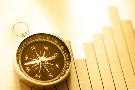 financial graphs: Diagram concept with compass and arrow in sepia toning Stock Photo