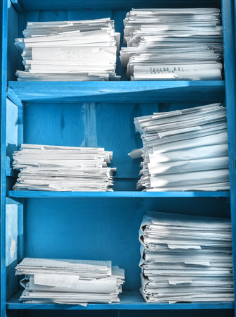 Paper documents stacked in archive on shelf photo
